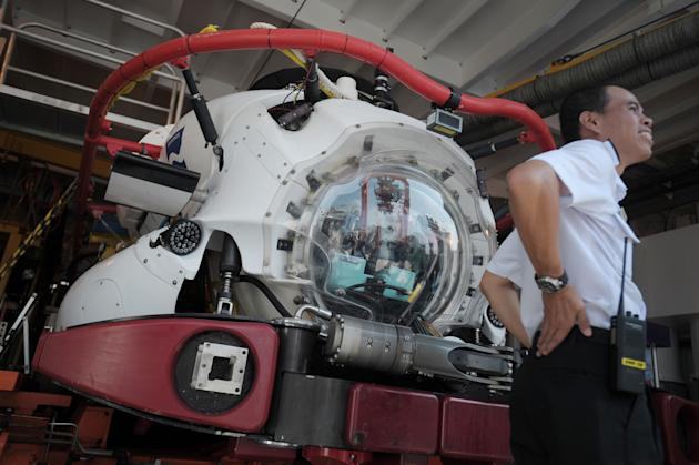 A Singapore naval officer stretches by a Submarine Rescue Vehicle on board the MV Swift Rescue, a private submarine rescue vessel contracted to the Republic of Singapore Navy on Thursday May 19, 2011 in Singapore during the International Maritime Defense Show.