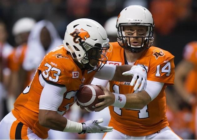 B.C. Lions' quarterback Travis Lulay, right, hands off to Andrew Harris during the first half of a CFL football game against the Toronto Argonauts in Vancouver, B.C., on Friday July 24, 2015. A ro