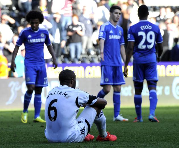 Swansea City's Ashley Williams sits on the turf at the end of their English Premier League soccer match against Chelsea at the Liberty Stadium in Swansea
