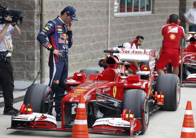 Red Bull Formula One driver Webber looks at the car of Ferrari Formula One driver Alonso after the qualifying session for the Korean F1 Grand Prix in Yeongam