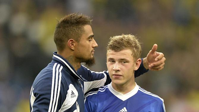 Schalke's Kevin-Prince Boateng reacts to Max Meyer after losing the German  Bundesliga soccer  match between FC Schalke 04 and Borussia Dortmund in Gelsenkirchen, Germany, Saturday, Oct. 26, 2013