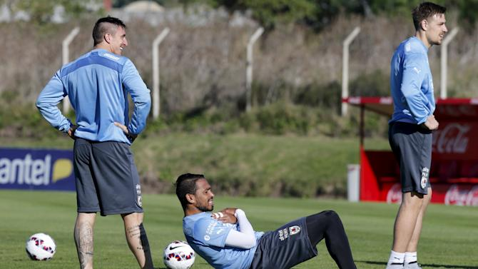 Uruguay's National soccer team player Pereira makes sit up alongside team mates Rodriguez and Coates during training at the team's headquarters in the outskirts of Montevideo