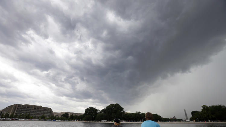 Kidwell Blanchard, left, 12, of Chandler, Ariz., sits with Andrew Sisk, 17, of Salt Lake City, Utah, as a storm moves through the area with the Washington Monument in the background, Thursday, June 13, 2013, in Washington. (AP Photo/Alex Brandon)