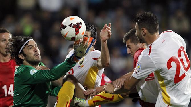 Serbia's goalkeeper Vladimir Stojkovic, left , challenges for the ball with Macedonia's Boban Grncarov, center and Jovan Kostovski during their World Cup 2014 Group A qualifying soccer match at the City Stadium in Jagodina, Serbia, Tuesday, Oct. 15, 2013