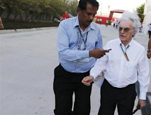 Bernie Ecclestone's hair blows in the wind while being interviewed as he walks at the paddock after the third practice session of the Bahrain F1 Grand Prix at the Bahrain International Circuit (BIC) in Sakhir