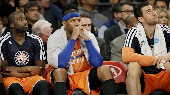 New York Knicks' Raymond Felton, left, Carmelo Anthony, center, and Andrea Bargnani look on from the bench during the second half of the NBA basketball game against the San Antonio Spurs at Madison Square Garden, Sunday, Nov. 10, 2013, in New York