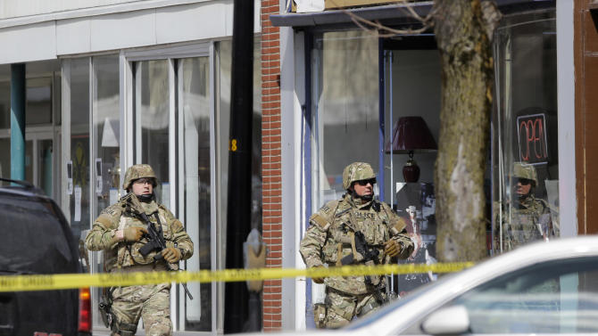 Law enforcement officers walk along Main Street in Herkimer, N.Y., while searching for a suspect in two shootings that killed four and injured at least two on, Wednesday, March 13, 2013. Authorities were looking for Kurt Meyers, said Joseph Malone, the police chief for Herkimer and Mohawk. Officials say guns and ammunition were found inside his Mohawk apartment after emergency crews were sent to a fire there Wednesday morning.  (AP Photo/Mike Groll)