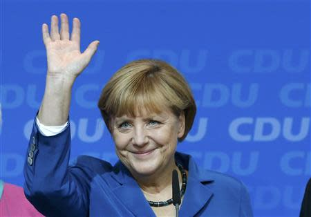 German Chancellor and leader of CDU Merkel waves to supporters after first exit polls in the German general election (Bundestagswahl) at the CDU party headquarters in Berlin