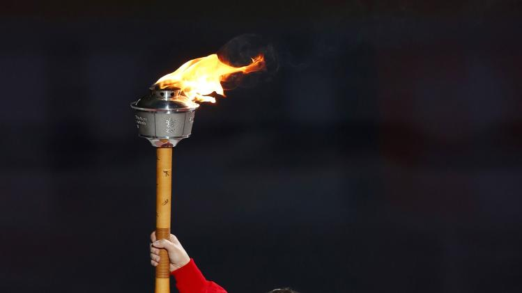 Ainsworth carries the Calgary Olympic torch before the start of the Dallas Stars and Calgary Flames NHL hockey game in Calgary.