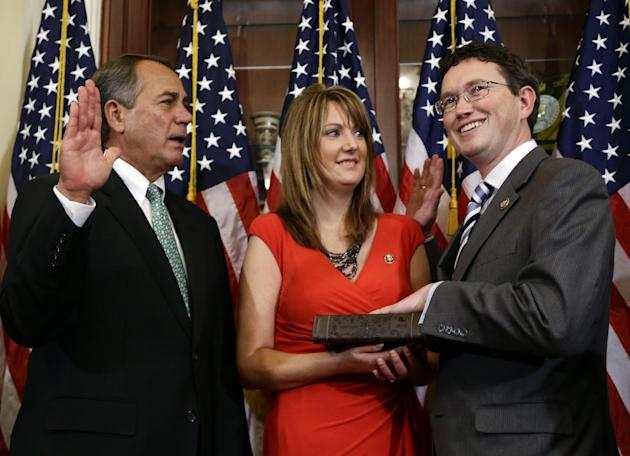 FILE - In this Nov. 13, 2012 file photo, House Speaker John Boehner of Ohio, left, administers the House oath during a mock swearing in ceremony for Rep. Thomas Massie, R-Ky., right, with his wife Rho