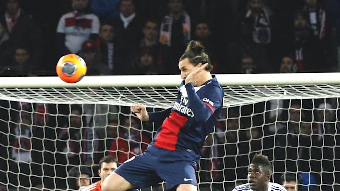 Paris Saint Germain's Zlatan Ibrahimovic of Sweden, center, heads the ball as Lyon's goalkeeper Remy Vercoutre, left, and Samuel Um Titti look on during their French League One soccer match, Sunday Dec. 1, 2013, in Parc des Princes stadium, in Paris, France