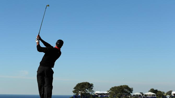 Tiger Woods hits his second shot on the 14th hole during the final round of the Farmers Insurance Open on the South Course at Torrey Pines Golf Course on January 28, 2013 in La Jolla, California. Photo by Stephen Dunn