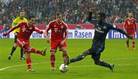 Bayern Munich's Thiago and Shaqiri fight for the ball with Hamburger SV's Djourou during German Bundesliga match in Munich