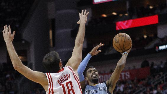 Memphis Grizzlies guard Mike Conley (11) drives to the basket as Houston Rockets' Omri Casspi (18) defends during the first half of an NBA basketball game Thursday, Dec. 26, 2013, in Houston