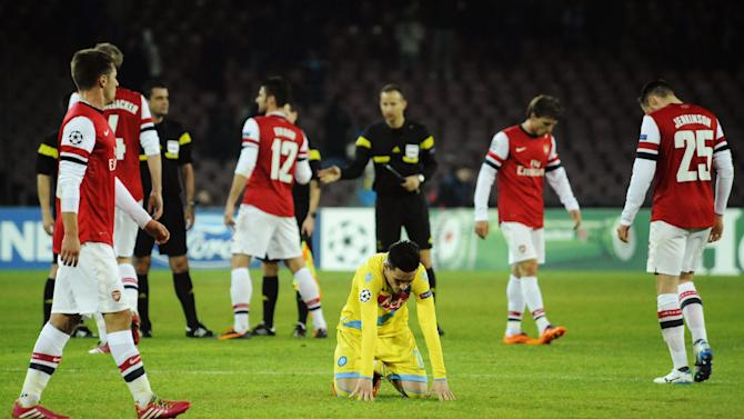 Napoli's Jose Callejon kneels on the field at the end of a Champions League, group F, soccer match between Napoli and Arsenal, at the Naples San Paolo stadium, Italy, Wednesday, Dec. 11, 2013. Ten-man Arsenal advanced to the Champions League knockout phase for the 14th consecutive year despite a 2-0 loss Wednesday at Napoli, which was eliminated. Gonzalo Higuain scored in the 73rd minute but the San Paolo stadium was soon silenced when word arrived that Borussia Dortmund had scored a late goal in a 2-1 win at Marseille to win Group F