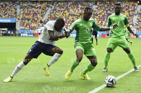 France's Matuidi fights for the ball with Nigeria's Onazi and Yobo during their 2014 World Cup round of 16 game at the Brasilia national stadium in Brasilia
