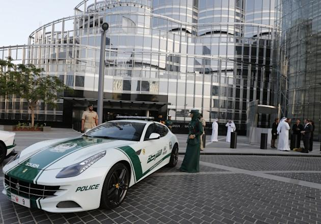 An Emirati female police officer stands near a Ferrari police vehicle at the foot of the Burj Khalifa tower in the Gulf emirate of Dubai on April 25, 2013. Two weeks after introducing the Lamborghini
