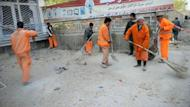 City workers clear the scene of a car suicide attack near the building from which insurgents attacked in front of the parliament in Kabul