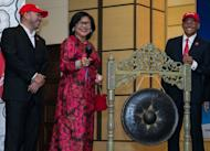 Independent non-executive chairman of AirAsia X Rafidah Aziz (C) prepares to hit a gong to mark the firm's listing debut alongside CEO Azran Osman-Rani (R) and director Kamarudin Meranun at the stock exchange in Kuala Lumpur on July 10, 2013. Shares in the long-haul budget carrier ended flat on their market debut, despite Osman-Rani promising a spending spree on new planes