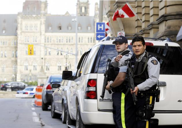Armed RCMP officers guard access to Parliament Hilll following a shooting incident in Ottawa