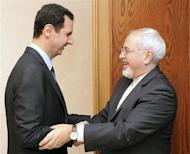 Syria's President Bashar al-Assad (L) welcomes Iran's Foreign Minister Mohammad Javad Zarif before a meeting in Damascus January 15, 2014, in this handout released by Syria's national news agency SANA. REUTERS/SANA/Handout via Reuters