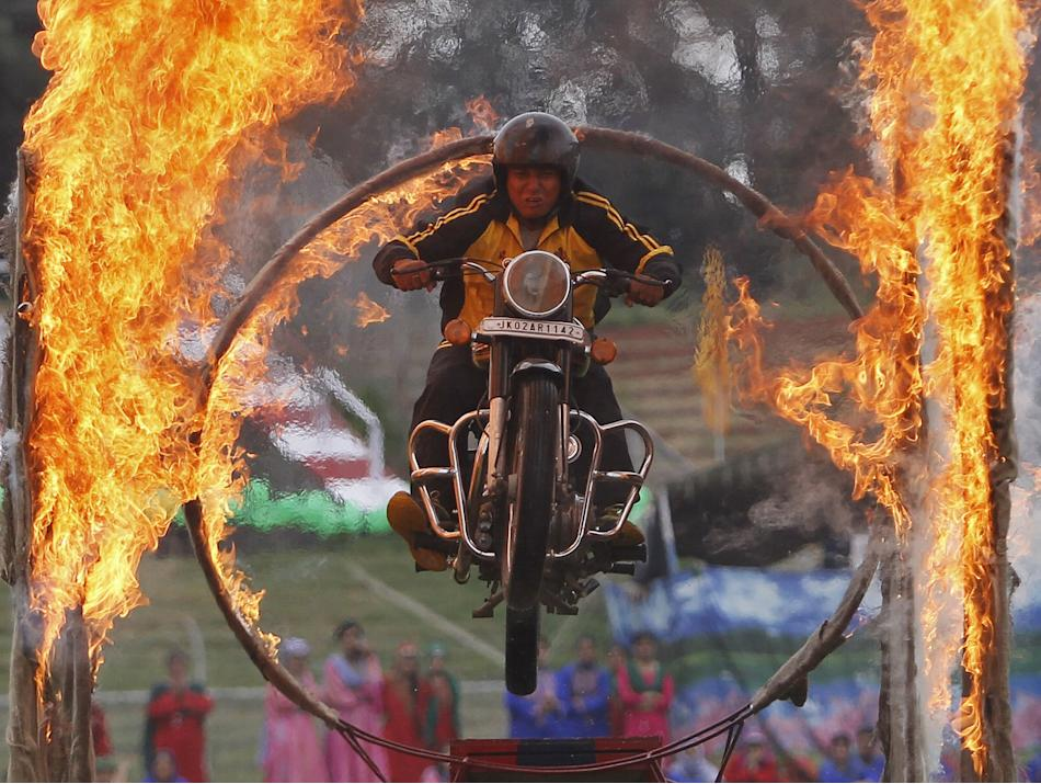 A Kashmiri policeman performs a stunt on a motorbike through a ring of fire during India's Independence Day celebrations in Srinagar