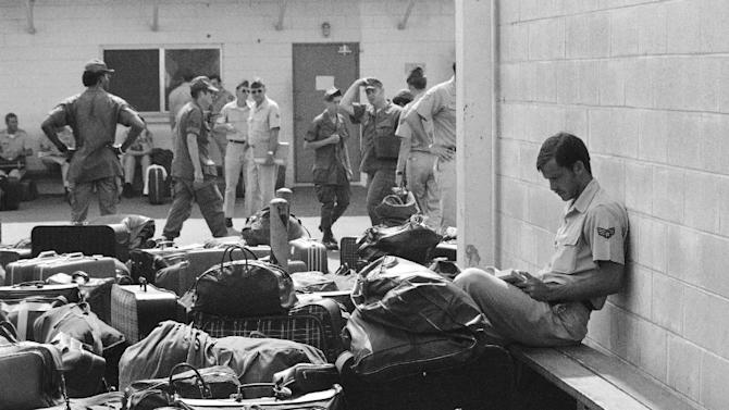 In this March 27, 1973 photo, surrounded by luggage of other departing GIs, U.S. Air Force airman reads paperback novel as he waits to begin processing at Camp Alpha on Saigon's Tan Son Nhut airbase in Saigon as troop withdrawals resume after 10 day-delay. More than 900 will leave with all U.S. troops out by Thursday. As the last U.S. combat troops left Vietnam 40 years ago, angry protesters still awaited them at home. North Vietnamese soldiers took heart from their foes' departure, and South Vietnamese who had helped the Americans feared for the future. While the fall of Saigon two years later — with its indelible images of frantic helicopter evacuations — is remembered as the final day of the Vietnam War, Friday marks an anniversary that holds greater meaning for many who fought, protested or otherwise lived it. (AP photo/Charles Harrity)