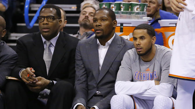 FILE - In this March 4, 2015, file photo, injured Oklahoma City Thunder forward Kevin Durant, center, watches from the bench with guard D.J. Augustin, right, and assistant coach Mark Bryant, left, during the first quarter of an NBA basketball game against the Philadelphia 76ers in Oklahoma City. Durant will have bone graft surgery next week to deal with a fractured bone in his right foot, and he will miss the rest of the season, the Oklahoma City Thunder announced Friday, March 27, 2015. (AP Photo/Sue Ogrocki, File)