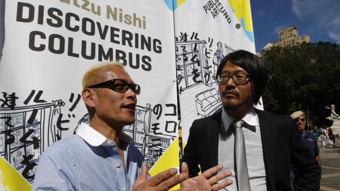 "Japanese artist Tatzu Nishi, left, speaks to reporters with the help of translator Kasuke Fujitaka during a media preview of ""Discovering Columbus,""  Wednesday, Sept. 19, 2012 in New York.  The 810-square-foot living room offers spectacular views of mid-Manhattan. A 13-foot statue of Christopher Columbus stands amid the couches, lamps and coffee table. (AP Photo/Mary Altaffer)"