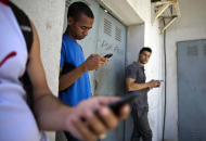 "Students gather behind a business looking for a Internet signal for their smart phones in Havana, Cuba, Tuesday, April 1, 2014. The U.S. Agency for International Development masterminded the creation of a ""Cuban Twitter,"" a communications network designed to undermine the communist government in Cuba, built with secret shell companies and financed through foreign banks, The Associated Press has learned. The project, which lasted more than two years and drew tens of thousands of subscribers, sought to evade Cuba's stranglehold on the Internet with a primitive social media platform. Its users were neither aware it was created by a U.S. agency with ties to the State Department, nor that American contractors were gathering personal data about them. In 2012, the text messaging service vanished as mysteriously as it appeared. (AP Photo/Ramon Espinosa)"