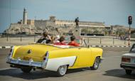 Tourist take a ride in a fully restored Mercury along the coast in Havana on March 18, 2013