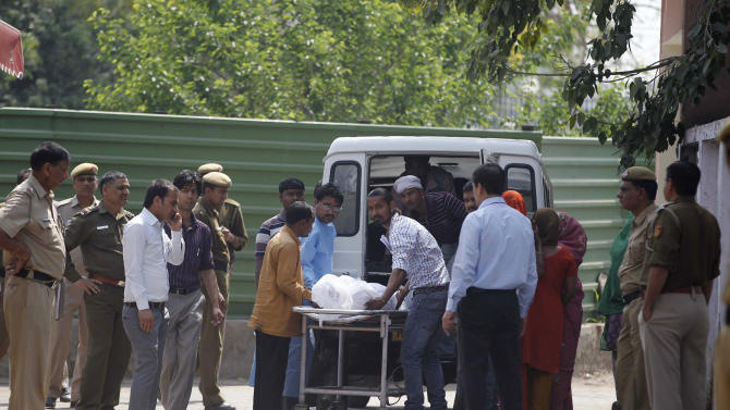 Unidentified relatives of Ram Singh, one of the men on trial for his alleged involvement in the gang rape and fatal beating of a woman aboard a New Delhi bus, carry Singh's body in to a waiting hearse outside a mortuary in New Delhi, India, Tuesday, March 12, 2013. The body of a man who died in a New Delhi jail while in the midst of a high-profile rape trial was released to his family Tuesday after a post-mortem exam aimed at determining whether he committed suicide or was killed.(AP Photo/ Mustafa Quraishi)