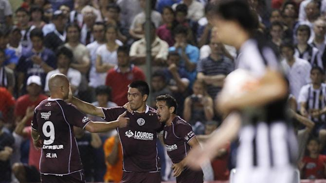 Paolo Goltz of Argentina's Lanus, third from left, celebrates with teammate Lautaro Acosta, right and Santiago Silva (9) after scoring against Paraguay's Libertad by a penalty during a Copa Sudamericana soccer game in Asuncion, Paraguay, Thursday, Nov. 21, 2013
