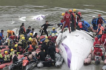 Emergency personnel try to extract passengers from a commercial plane after it crashed in Taipei, Taiwan.