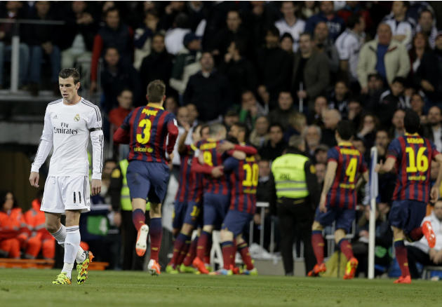 Real Madrid's Gareth Bale, left walks away as FC Barcelona players celebrate FC Barcelona's Andres Iniesta's goal during a Spanish La Liga soccer match at the Santiago Bernabeu stadium in