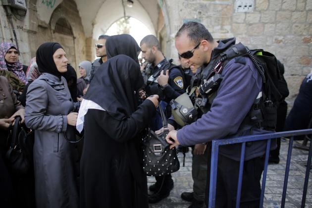 An Israeli policeman checks the bag of a Palestinian woman before she enters the compound which houses al-Aqsa mosque in Jerusalem's Old City