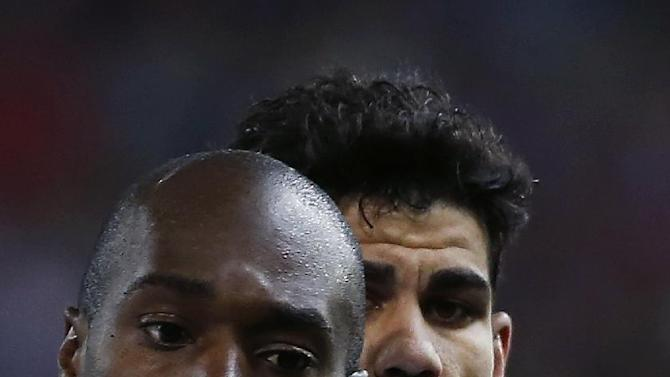 Atletico's Diego Costa, right, vies for the ball with Granada's Nyom during their Spanish La Liga soccer match at the Vicente Calderon stadium in Madrid, Spain, Wednesday, March 26, 2014