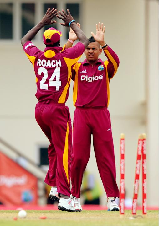 West Indies cricketers Kemar Roach (L) a