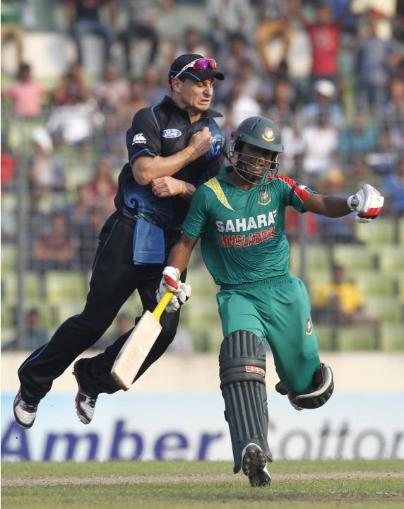 Bangladesh's Naeem Islam and New Zealand's Nathan McCullum collide during their first one-day international (ODI) cricket match in Dhaka