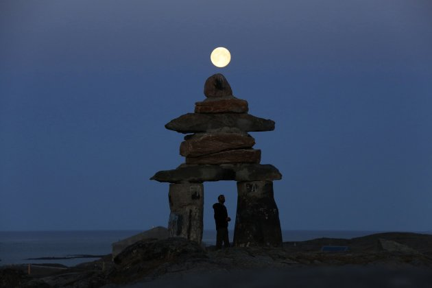 A man looks at a giant inukshuk as the moon rises above it in Rankin Inlet, Nunavut in this file photo from August 21, 2013. The inukshuk is a stone landmark or cairn used by the Inuit people in the arctic. Canada's Arctic territory of Nunavut has opened long-awaited talks with the federal government on gaining control of the region's vast natural resources, a move that could boost exploration and development.  REUTERS/Chris Wattie/Files   (CANADA - Tags: SOCIETY ENVIRONMENT)