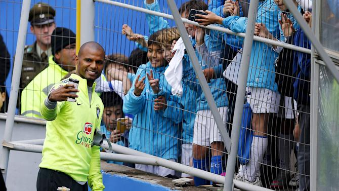 Brazil's goalkeeper Jefferson takes a selfie with children after a team training session ahead of their 2018 World Cup qualifying match against Chile this Thursday in Santiago