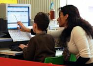 """File picture shows a teacher helping a child use Twitter at a school in France. Twitter said a """"cascading bug"""" caused outages affecting millions of users of the wildly popular site, and dismissed claims of a hacker attack"""