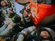 A screen grab taken from the large video screen at the Jiuquan Space Centre on June 29, 2012 shows Chinese astronauts in the Shenzhou-9 spacecraft as it prepared for reentry to earth's atmosphere