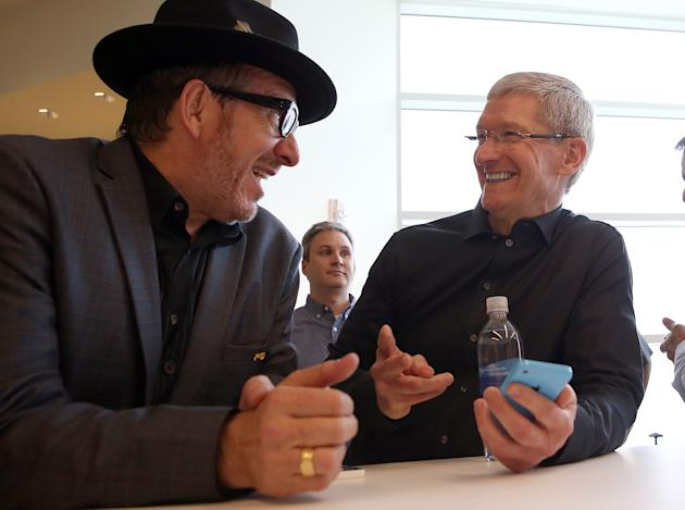 CUPERTINO, CA - SEPTEMBER 10: Musician Elvis Costello (L) and Apple CEO Tim Cook look at the new iPhone 5C during an Apple product announcement at the Apple campus on September 10, 2013 in Cupertino, California. The company launched the new iPhone 5C model that will run iOS 7 is made from hard-coated polycarbonate and comes in various colors and the iPhone 5S that features fingerprint recognition security. (Photo by Justin Sullivan/Getty Images)
