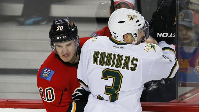 Dallas Stars' Robidas hits Calgary Flames Glencross against the boards during their NHL hockey game in Calgary.