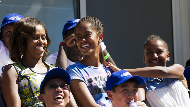 First Lady Michelle Obama, left, alongside her daughters Malia, center, and Sahsa attend the 18th Annual Arthur Ashe Kids' Day, the kick off to the 2013 US Open tennis tournament, on Saturday, Aug. 24, 2013 in New York. (Photo by Charles Sykes/Invision/AP)