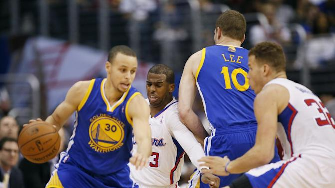 Golden State Warriors' David Lee, second from right, puts a pick on Los Angeles Clippers' Chris Paul, as Warriors' Stephen Curry, left, controls the ball toward a defending Clippers' Blake Griffin, right, during the first half of an NBA basketball game in Los Angeles, Wednesday, March 12, 2014
