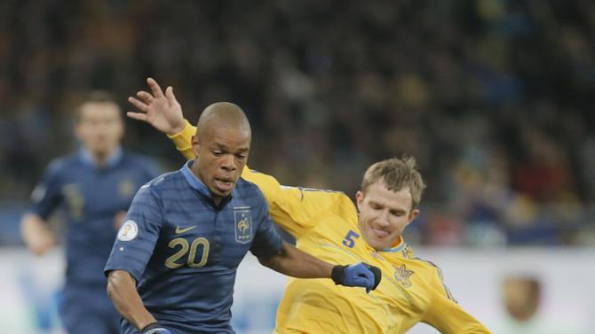 France's Loic Remy, left, and Ukraine's Olexandr Kucher battle for the ball during their  2014 World Cup qualifying soccer match at the Olympiyskiy national stadium in Kiev, Ukraine, Friday, Nov. 15, 2013