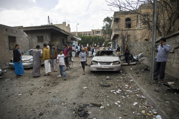 People gather at a site hit by a Saudi-led airstrike in Sanaa, Yemen, Wednesday, May 27, 2015. In a new report Wednesday, World Health Organization Chief Margaret Chan said that Yemen's conflict h