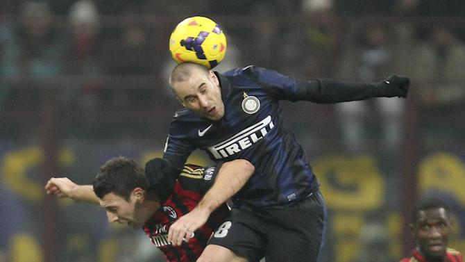 Inter Milan forward Rodrigo Palacio, top, of Argentina, jumps for the ball with AC Milan defender Daniele Bonera during a Serie A soccer match, at the San Siro stadium in Milan, Italy, Sunday, Dec. 22, 2013